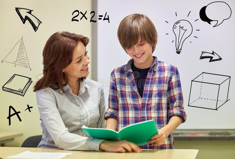 Skolapojke med anteckningsboken och läraren i klassrum arkivfoton