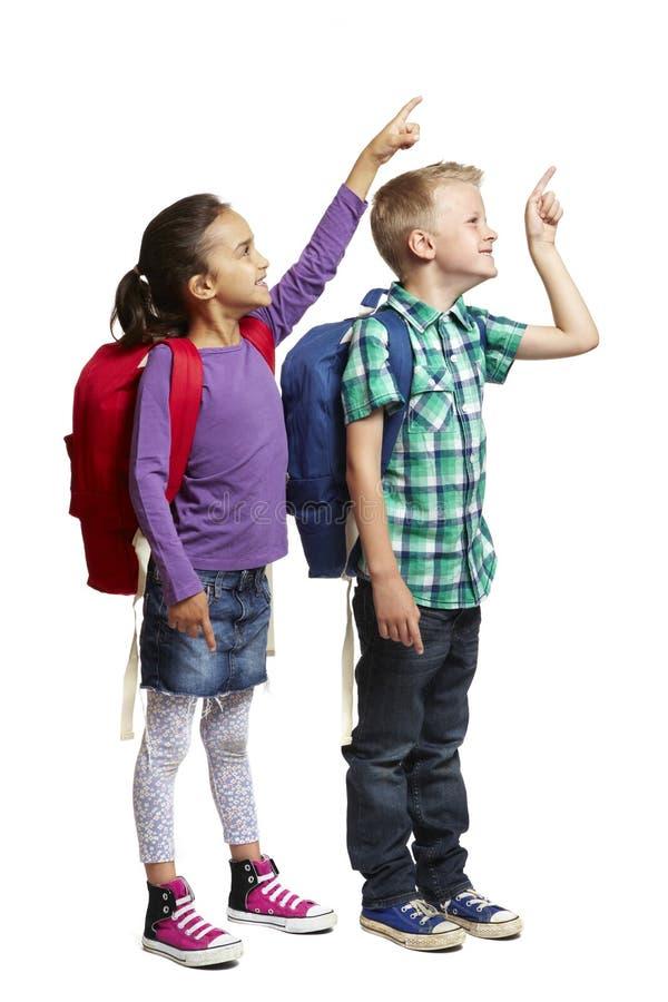 Skolapojke och flicka med att peka för ryggsäckar royaltyfri fotografi