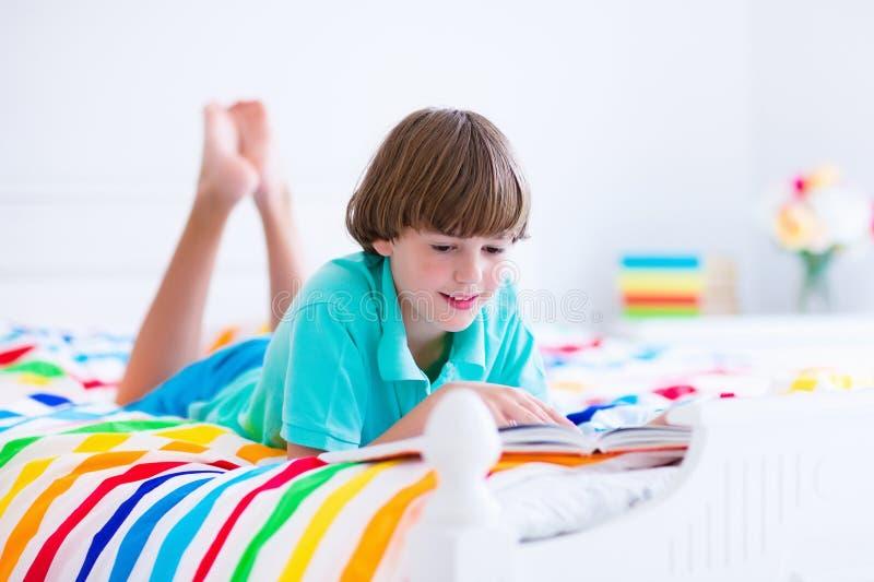 Skolapojke som läser en bok i säng royaltyfri fotografi