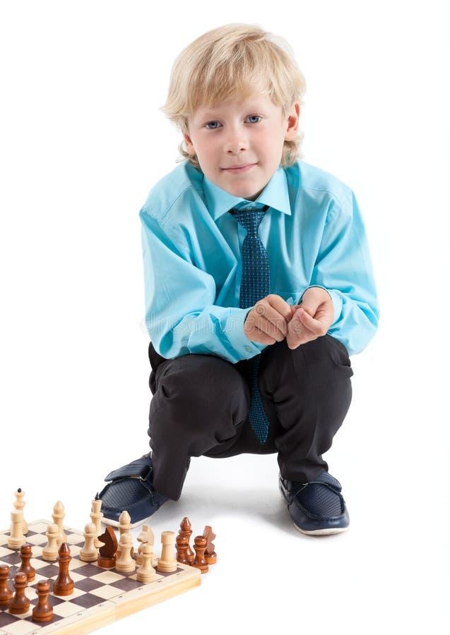 Skolapojken i skjorta och bandet som sitter nära schackbrädet som ser kameran, isolerade vit bakgrund arkivbild