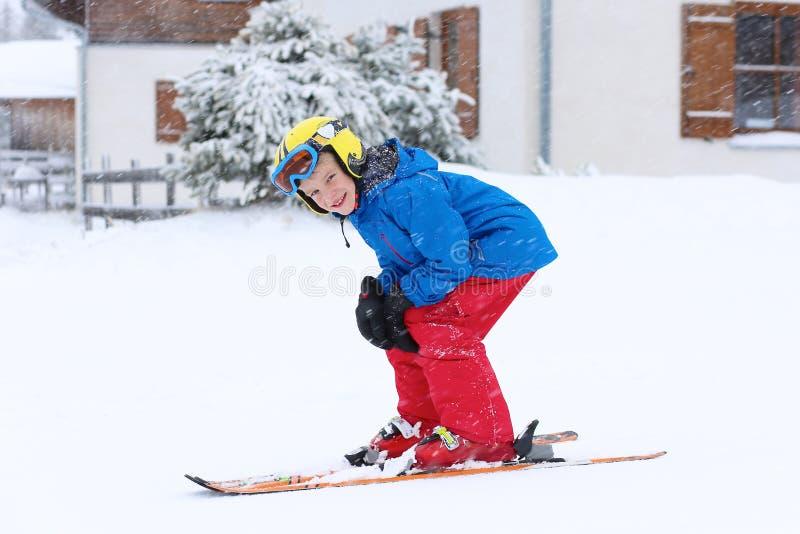 Skolapojken som tycker om vinter, skidar semestern arkivfoto