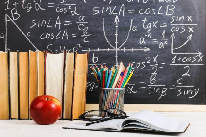 Skolaskrivbord i klassrum, med b?cker p? bakgrund av kritabr?det med skriftliga formler Soncept l?rares dag arkivbild