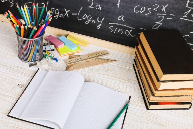 Skolaskrivbord i klassrum, med b?cker p? bakgrund av kritabr?det med skriftliga formler Soncept l?rares dag arkivfoton