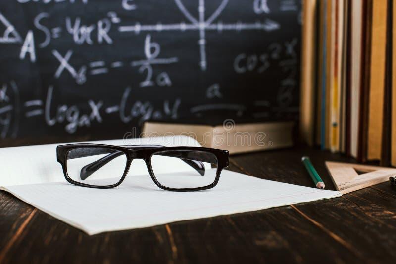 Skolaskrivbord i klassrum, med b?cker p? bakgrund av kritabr?det med skriftliga formler Soncept l?rares dag royaltyfri bild