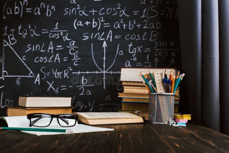 Skolaskrivbord i klassrum, med b?cker p? bakgrund av kritabr?det med skriftliga formler Soncept l?rares dag royaltyfri fotografi