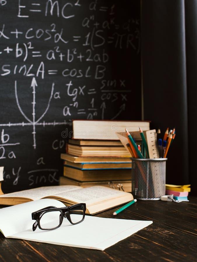 Skolaskrivbord i klassrum, med b?cker p? bakgrund av kritabr?det med skriftliga formler Soncept l?rares dag royaltyfria bilder
