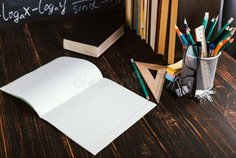 Skolaskrivbord i klassrum, med b?cker p? bakgrund av kritabr?det med skriftliga formler Soncept l?rares dag Kopieringsspase arkivbilder