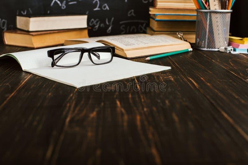 Skolaskrivbord i klassrum, med b?cker p? bakgrund av kritabr?det med skriftliga formler Soncept l?rares dag Kopieringsspase royaltyfri foto