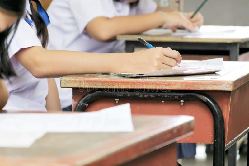 Skolastudent` s som tar examen skriva svar i klassrumet för edu royaltyfri foto