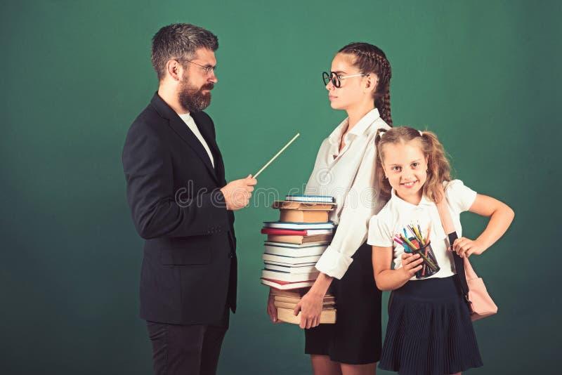 Skolatid av systrar och fadern i arkiv skolakurs med den strikta l?raren och smarta flitiga studenter arkivfoton