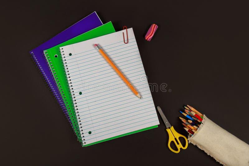 Skolatillförsel, anteckningsböcker, kulöra blyertspennor, sax på den svarta tabellen fotografering för bildbyråer