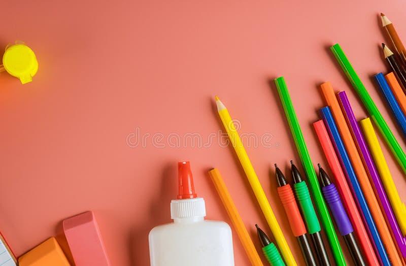 Skolatillförsel, bästa gräns för kulöra blyertspennor på en rosa bakgrund arkivbild