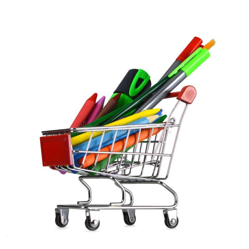 Skolatillförsel i shoppingvagn på vit arkivfoton
