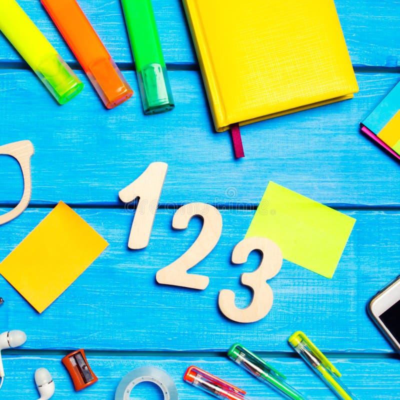 Skolatillf?rsel i skolaskrivbordet, brevpapper, skolabegrepp, bl? bakgrund, id?rikt kaos, utrymme f?r text, mark?rer, pennor, arkivfoto