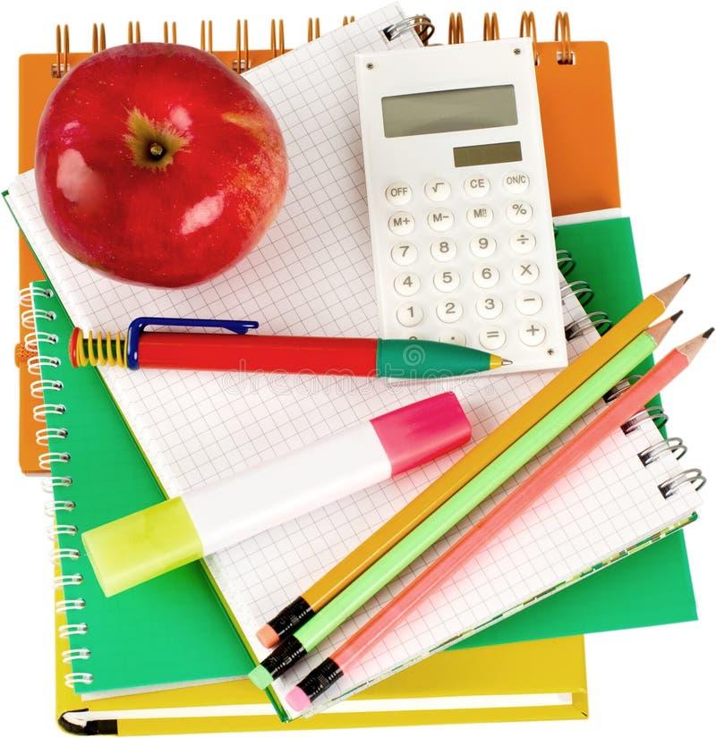 Skolatillförsel med ett äpple överst - isolerat arkivfoto