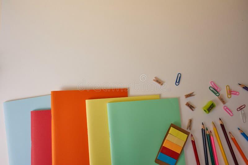 Skolatillförsel med färgrika blyertspennor och anteckningsböcker arkivfoton