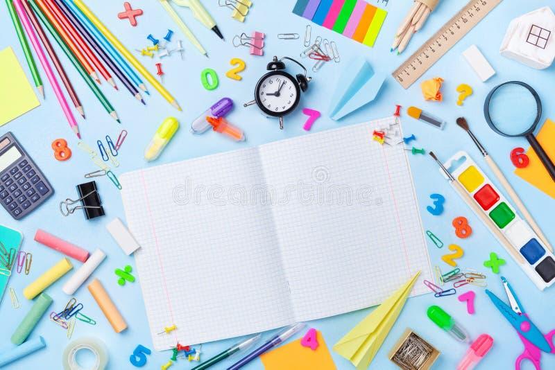 Skolatillförsel och brevpapper med den öppna anteckningsboken på blå bästa sikt för tabell Utbildning som lär och som är tillbaka royaltyfri foto