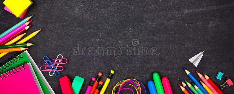 Skolatillförsel tränga någon gränsbanret, bästa sikt på en svart tavlabakgrund med kopieringsutrymme tillbaka skola till arkivfoto