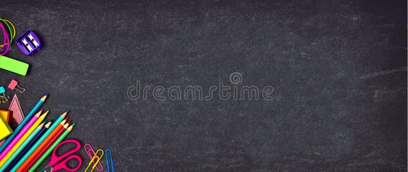 Skolatillförsel tränga någon gränsbanret, bästa sikt på en svart tavlabakgrund med kopieringsutrymme tillbaka skola till royaltyfri bild