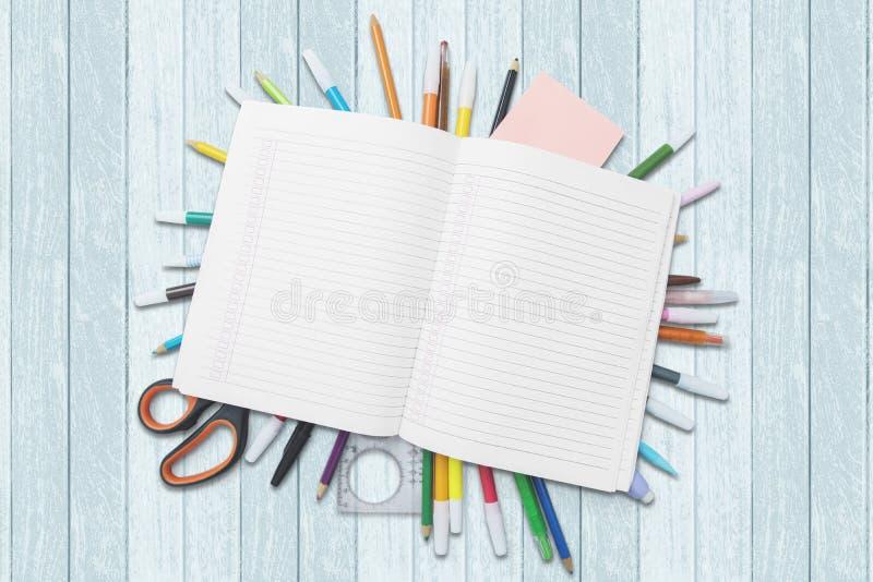 Skolatillförsel under den tomma boken på tabellen fotografering för bildbyråer