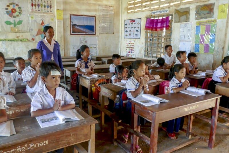 Skolaungar i klassrum av kampongen Tralach Cambodja royaltyfri fotografi