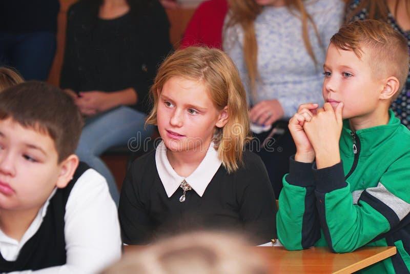 Skolaungar i klassrumet lyssnar till läraren royaltyfri fotografi