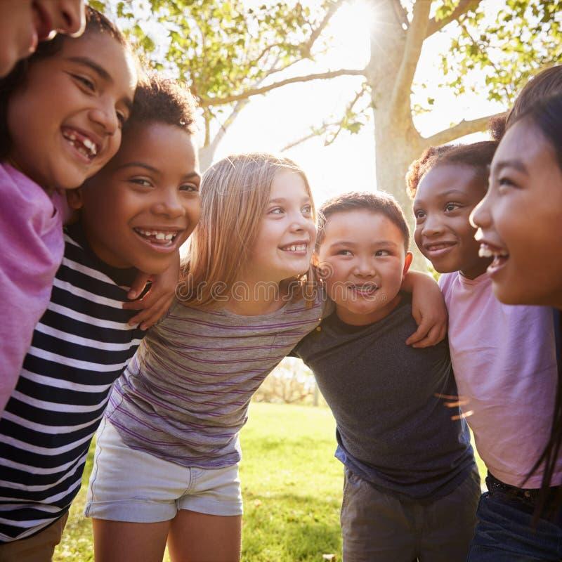 Skolaungar omfamnar anseendet i en cirkel, fyrkantigt format arkivbilder