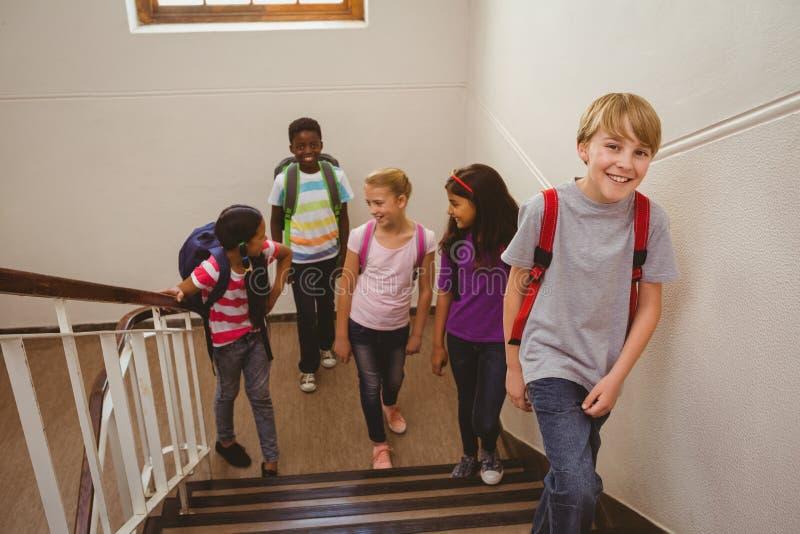 Skolaungar som går upp trappa i skola royaltyfria bilder