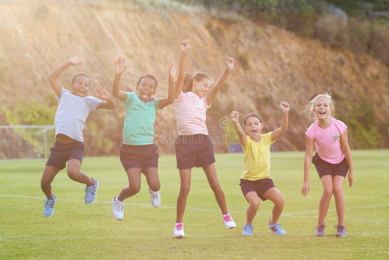 Skolaungar som har gyckel i lekplats arkivbilder
