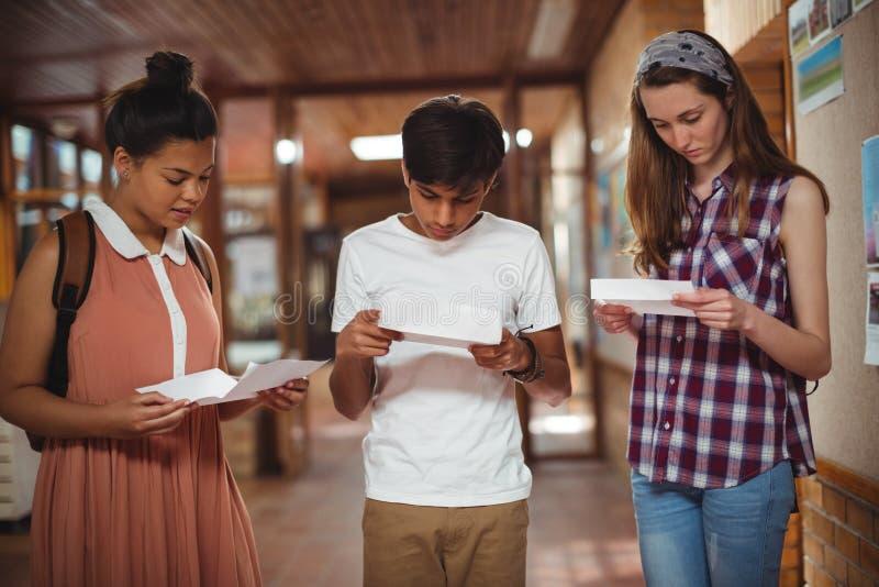 Skolaungar som kontrollerar frågepapper i korridor arkivfoton