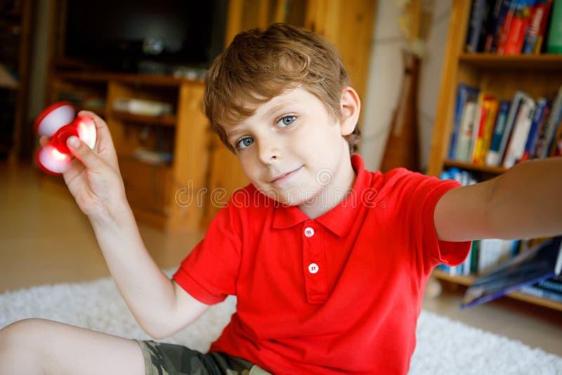 Skolaunge som spelar med den Tri rastlös människahandspinnaren inomhus arkivbild