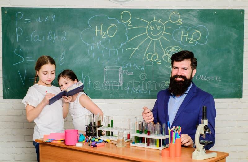 skolaungeforskare som studerar vetenskap tillbaka skola till lycklig barnl?rare Sm? ungar som l?r kemi i skola royaltyfria bilder