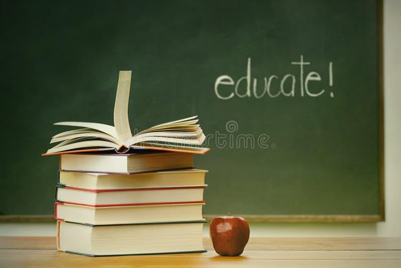 Skolböcker och äpple på skrivbordet royaltyfri fotografi