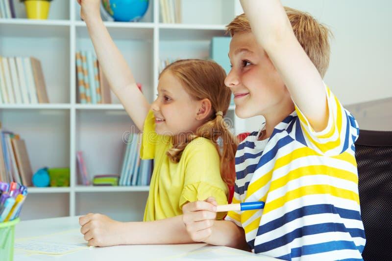 Skolbarn är kom tillbaka till skola och att lära på tabellen i klassrum arkivbilder