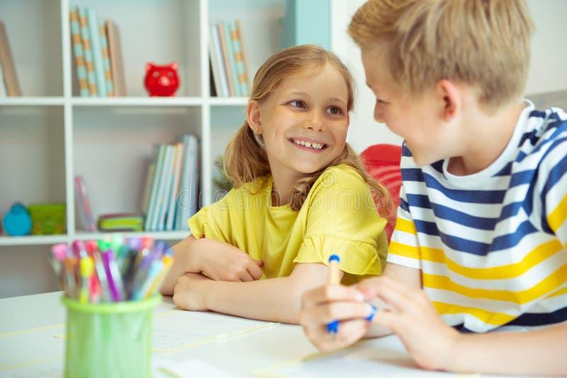 Skolbarn är kom tillbaka till skola och att lära på tabellen i klassrum arkivfoto