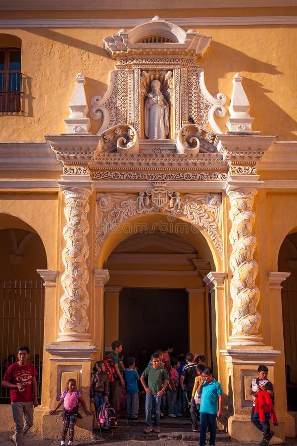 Skolbarn framme av den LaMerced kloster i Antigua royaltyfria foton