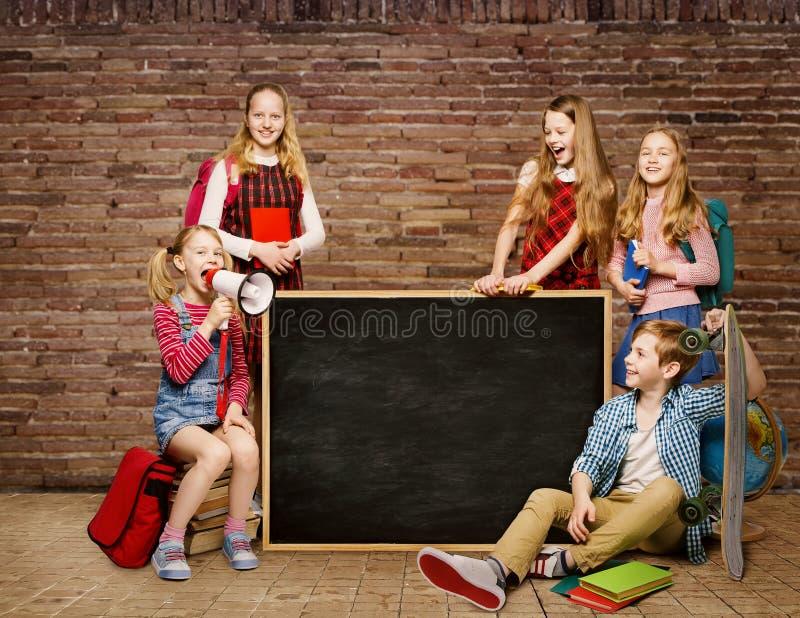 Skolbarn grupperar, ungestudenter runt om svart tavla, pojkeflicka arkivbild
