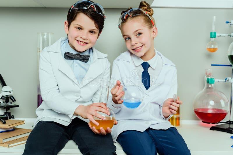 Skolbarn i vita lag som rymmer agens, i att sitta för flaskor arkivbilder