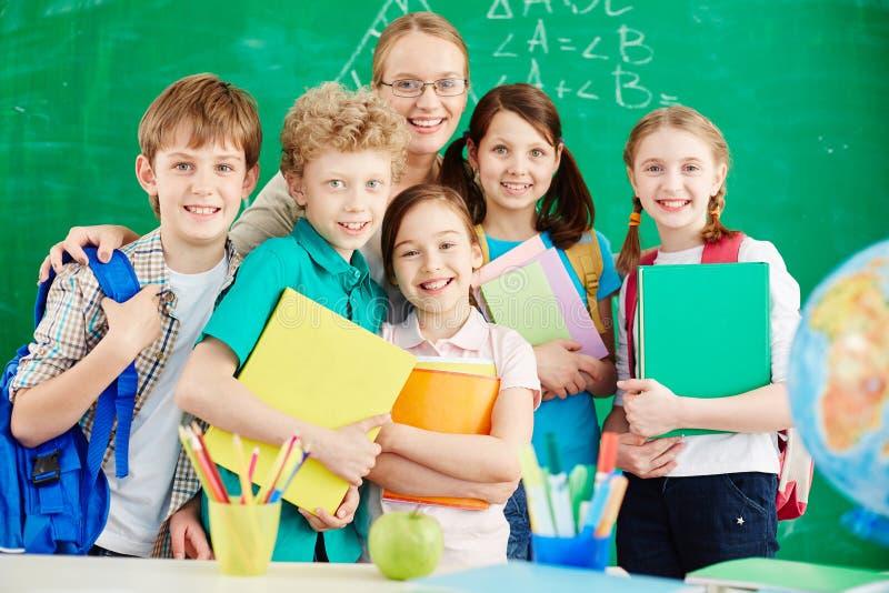 Skolbarn med läraren arkivbild