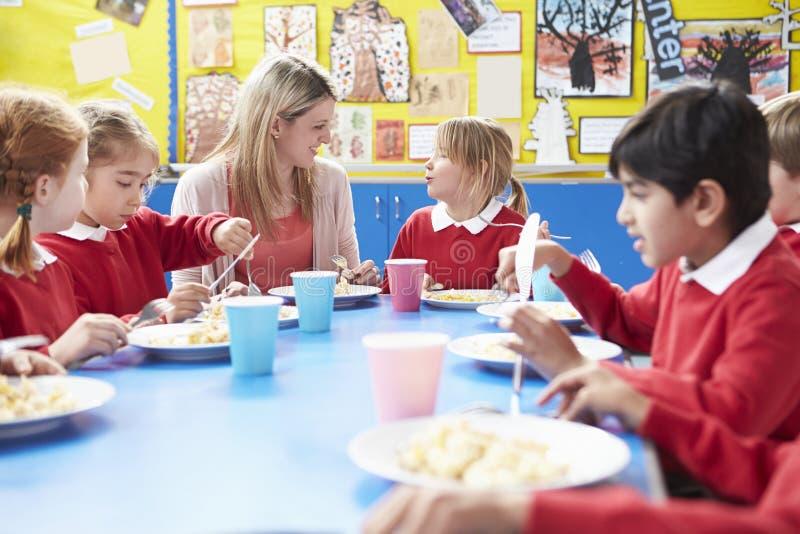 Skolbarn med läraren Sitting At Table som äter lunch fotografering för bildbyråer