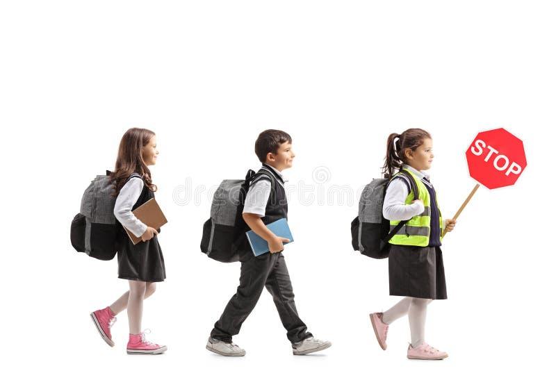 Skolbarn som går, en skolflicka som rymmer ett stopptecken royaltyfria foton