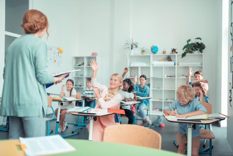 Skolbarn som gör summor med deras matematiklärare arkivfoto