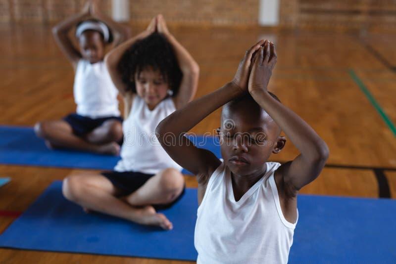 Skolbarn som gör yoga och mediterar på en yoga som är matt i skola royaltyfri foto