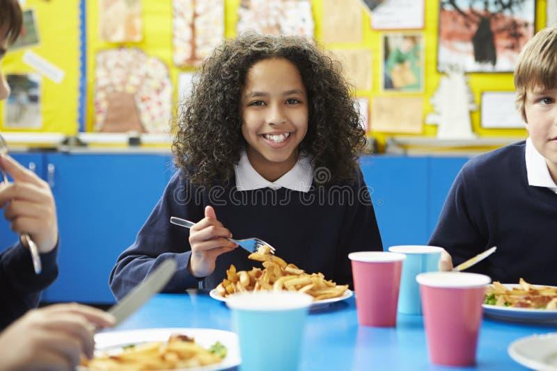 Skolbarn som sitter på tabellen som äter lagad mat lunch arkivbild