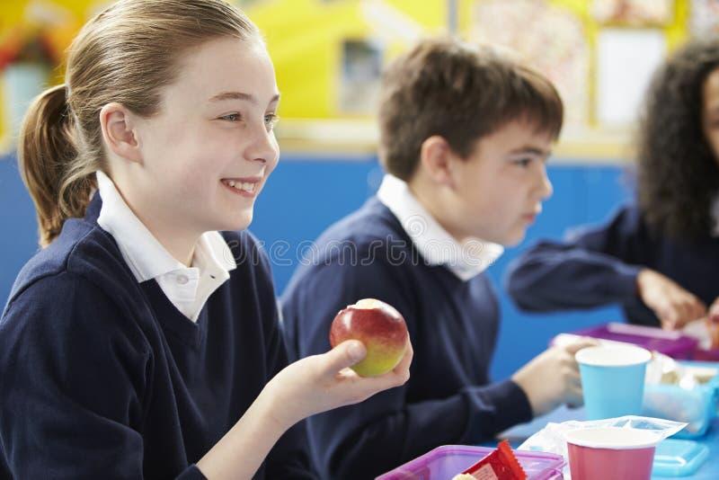 Skolbarn som sitter på tabellen som äter matsäck fotografering för bildbyråer