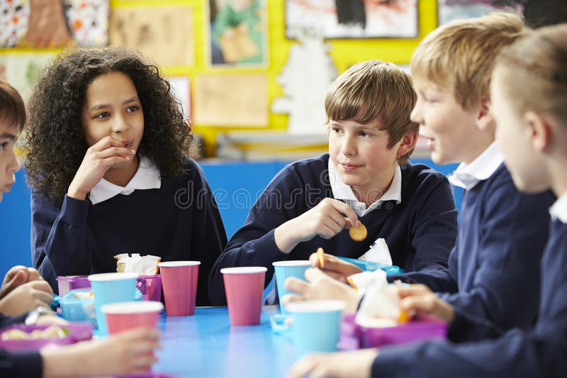Skolbarn som sitter på tabellen som äter matsäck arkivfoto