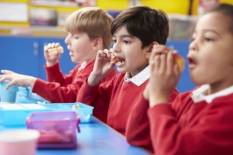 Skolbarn som sitter på tabellen som äter matsäck royaltyfri fotografi