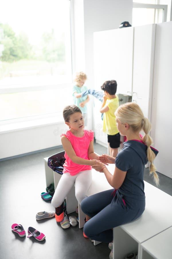 Skolbarn som spelar i ett ändrande rum royaltyfria foton