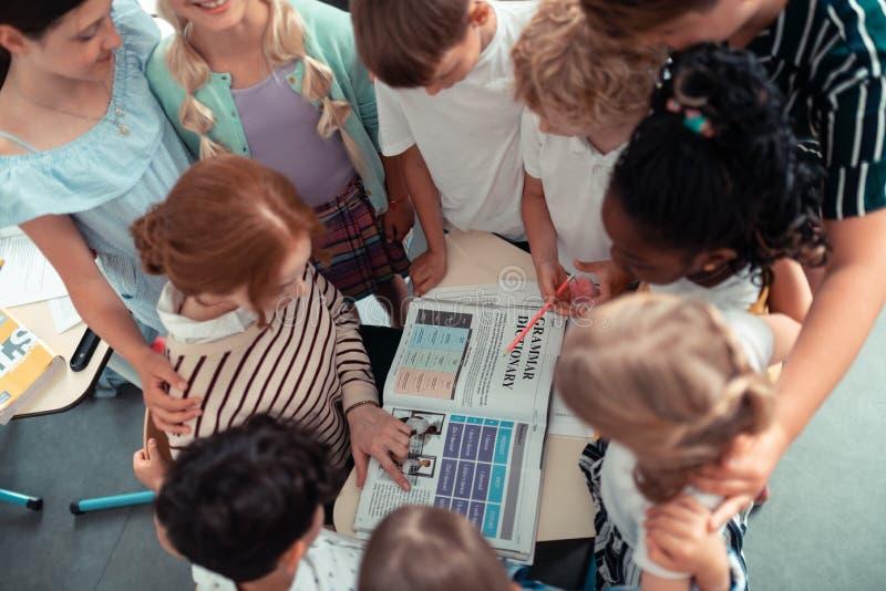 Skolbarn som står runt om deras lärareläsningregler arkivbilder