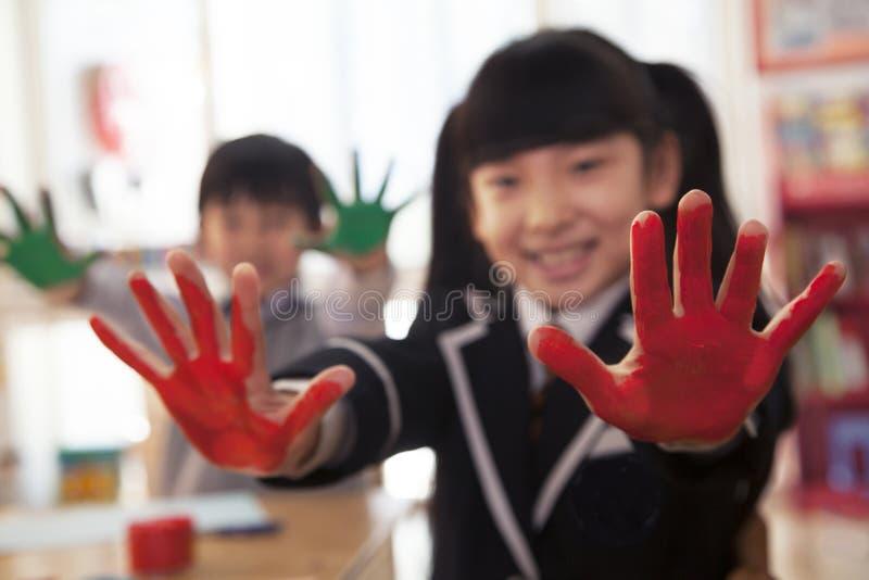 Skolbarn som visar deras täckte händer i målarfärg royaltyfria bilder